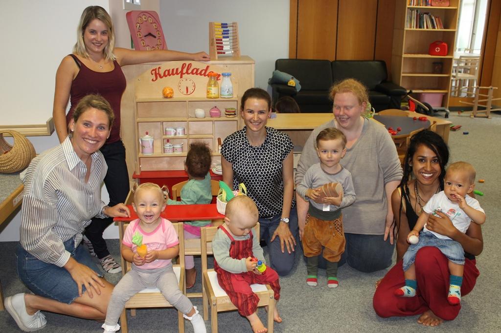 stv. Leiterin Lisa Geyer (sitzend links vom Kaufmannsladen) sowie Brigitte Baur (sitzend rechts vom Kaufmannsladen) freuten sich mit den Kindern und Eltern über die neuen Lebensmittel und Zubehör für den Kaufmannsladen